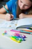 Barn som målar en färgläggningbok Ny trend för spänningsavlösning Royaltyfri Foto