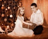 Barn som mottar gåvor under julgran. Arkivbild