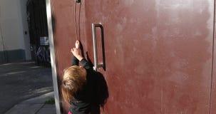 Barn som når hushögtalaranläggningknappen på dörröppningen lager videofilmer