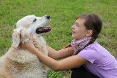 Barn som omfamnar hunden på en äng fotografering för bildbyråer