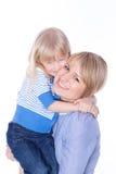 barn som omfamnar lyckligt le för mom Arkivbilder