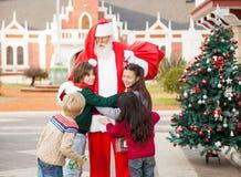 Barn som omfamnar Santa Claus Arkivbild