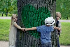 Barn som omfamnar trädet Utomhus- natur för miljöskydd Beskydd utomhus arkivfoto