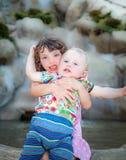 Barn som omkring bedrar Flickan kramar pysen utomhus Arkivfoto