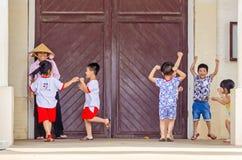 Barn som omkring spelar och stojar på ingången av en cathedr Arkivfoton