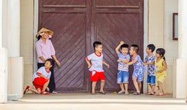 Barn som omkring spelar och stojar på ingången av en cathedr Royaltyfri Foto