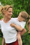 barn som på ryggen ger henne rittbarn för moder Arkivfoton