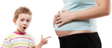 Barn som pekar hans gravida modermage Arkivfoto