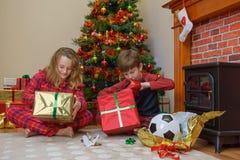 Barn som öppnar gåvor på julmorgon Arkivbild