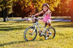 Barn som rider en cykel Ungen i hjälm på cykeln Royaltyfria Bilder