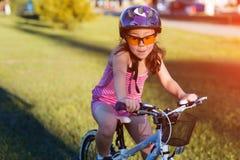 Barn som rider en cykel Ungen i hjälm på cykeln Royaltyfria Foton
