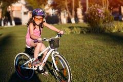 Barn som rider en cykel Ungen i hjälm på cykeln Arkivbild