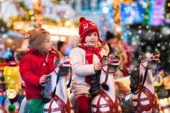 Barn som rider karusell på julmarknad Royaltyfri Foto