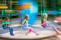 Barn som rider på en karusell royaltyfri foto