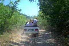 Barn som rider på smutsskogvägen Arkivfoto
