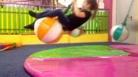 Barn som rotera på en gunga i underhållningmitten stock video