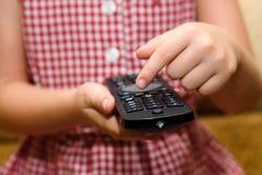 Barn som rymmer avlägsen TV arkivfoton