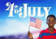 Barn som rymmer en amerikanska flaggan för 4th Juli Arkivfoto