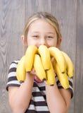 Barn som rymmer en grupp av bananer Arkivbild