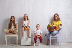 Barn som rymmer en korg av ny frukt och sund mat för grönsaker arkivfoton