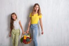Barn som rymmer en korg av ny frukt och sund mat för grönsaker royaltyfri fotografi
