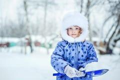 Barn som rymmer en skyffel som utomhus spelar i vinter Arkivbild