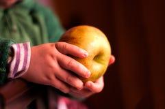 Barn som rymmer ett äpple i en hand Arkivfoto