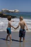 Barn som rymmer händer på stranden. arkivbild