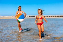 Barn som rymmer händer som kör på stranden Arkivbild