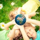 Barn som rymmer jordplaneten i händer Royaltyfri Fotografi