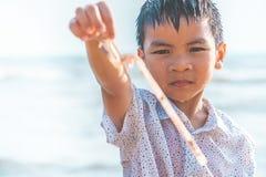 Barn som rymmer plast- sugr?r som han grundar p? stranden fotografering för bildbyråer