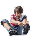 Barn som sätter på gymnastikskor Arkivbild