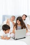 Barn som ser deras bärbar dator 库存图片
