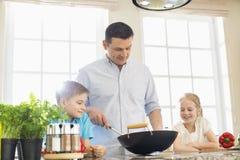 Barn som ser fadern som förbereder mat i kök royaltyfri fotografi