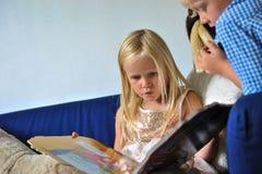 Barn som ser i bok Fotografering för Bildbyråer