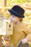 Barn som ser nyfiket på ett fågelhus Fotografering för Bildbyråer