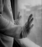 Barn som ser till och med fönstret med händer som läggas på exponeringsglaset Arkivfoto