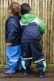 Barn som ser till och med staketet Arkivbilder