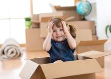 Barn som ser ut ur en ask i nytt rum, når att ha flyttat sig Royaltyfri Fotografi