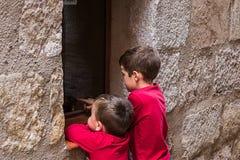 Barn som ser ut ur ett fönster av ett hus på gatan arkivbild