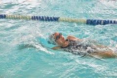 Barn som simmar fristil på att simma kurs royaltyfri fotografi