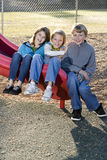 barn som sitter glidbana tre Royaltyfria Bilder