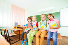 Barn som sitter i rad på skrivbordet med läroböcker Fotografering för Bildbyråer