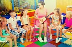 Barn som sitter med läraren och lyssnar till musik i grupp royaltyfri foto
