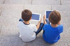 Barn som sitter med minnestavladatorer tillbaka sikt Utbildning som lär, teknologi, vänner, skolabegrepp Royaltyfri Fotografi