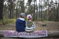 Barn som sitter på en inloggning höstskogen och väntar när Arkivbild