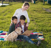 Barn som sitter på gräset och läseboken Fotografering för Bildbyråer