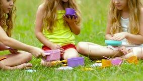 Barn som sitter på gräset som spelar med leksaker som gör suddig bakgrunden långsam rörelse close upp arkivfilmer