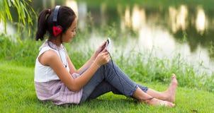 Barn som sitter på gräsmattan och, tycker om leken Royaltyfria Foton