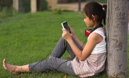 Barn som sitter på gräsmattan och, tycker om leken Arkivfoton